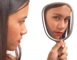 unhappy girl looking in mirror