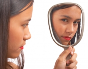 unhappy girl looking in mirror
