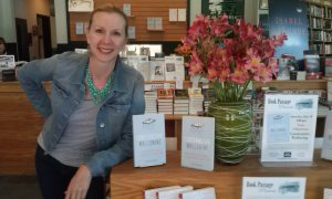 Tina with books on table in front of store