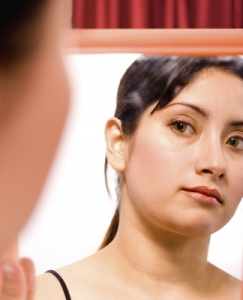 woman looking in mirror critically