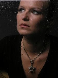 woman looking through rainy window