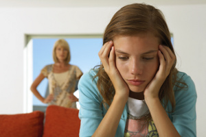 Girl, upset, with mother in background