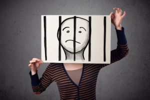 Woman holding paper sign with prison bars drawn in front of her face